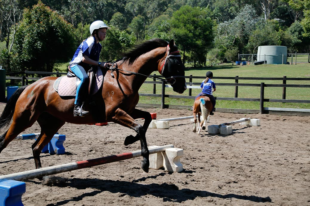 Two competitors, one jumping a cavaletti, the other steering between cavalettis. © Irma Havlicek
