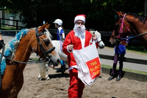 Santa brings a Reject Shop plastic bag filled with presents to give to the riders.