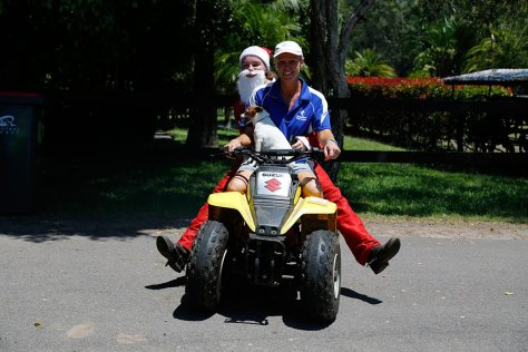 Sandie, with Timmy the small dog on her lap, give Santa a ride back to the house on a 4-wheeled motor.