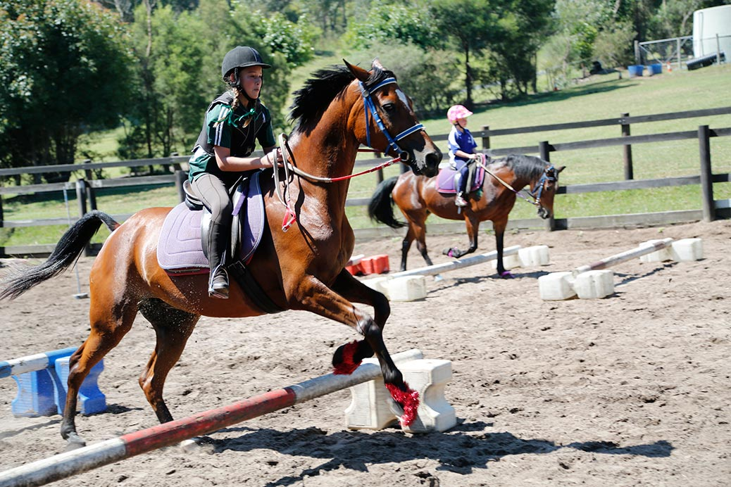 Two riders compete in two rows of cavalettis: the one in the foreground trotting over, the younger, less experienced rider in the background walking over the cavalettis