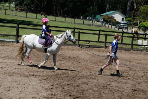 A young, less experienced rider is led through the course on a white pony