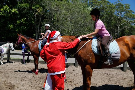 Santa gives a Christmas present to one of the riders on a chestnut horse