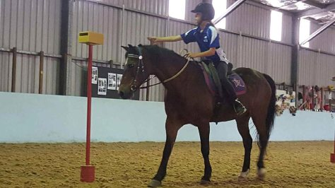 A young rider competes in a fun event that in an indoor arena during one of the HPRA summer camps