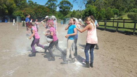 Girls throw flour at each other in one of the HorsePower Riding Academy's fun games during one of the 2016 January holiday camps.