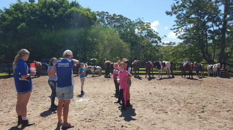 Riding instructors, young riders and the horses in the arena before the day's equestrian events begin.