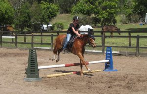 Jaycie, happily riding her pony, Tommy, over a jump