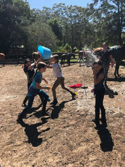 Camp participants enjoy a water fight in the arena